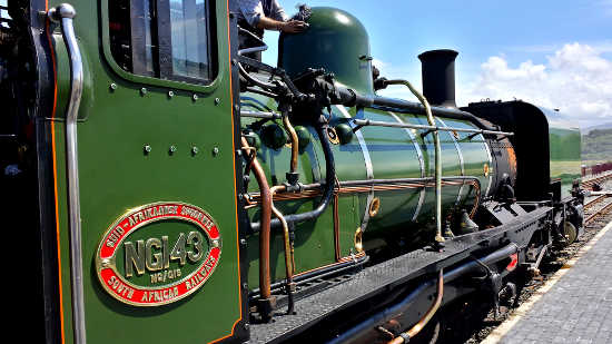 A green steam train at the railway station in Porthmadog, Wales, UK