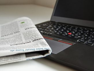 Newspaper and black Windows laptop computer