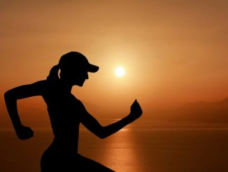 Woman running silhouette against the setting sun