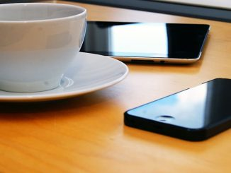 Coffee cup, iPhone and iPad on a table